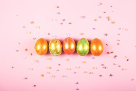 Five colored Easter eggs lie on a pink background among the gypsophila flowers.