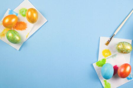 Only painted eggs of rakh flowers with a gold dusting dry on napkins next to a brush on a blue background. Copy space.