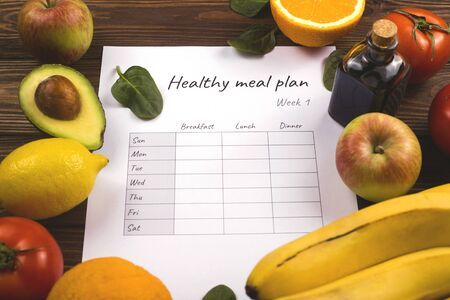 Healthy weekly meal plan among fresh organic fruits and vegetables cooking ingredients on wooden table.