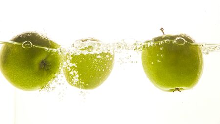 Green apples in the water with water splash on white background.
