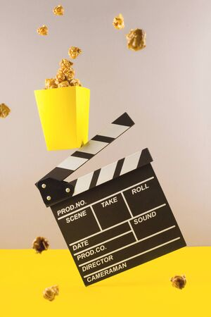 A movie clapper flies among popcorn. The concept of a cinema, relaxing watching movies and TV shows.