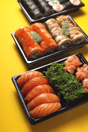 Sushi with fresh fish salmon and eel delivery in containers to the house on a bright yellow background.