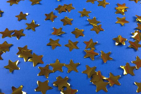 Gold shiny confetti in the shape of stars on a bright blue background. Festive and Christmas background. Top view, copy space