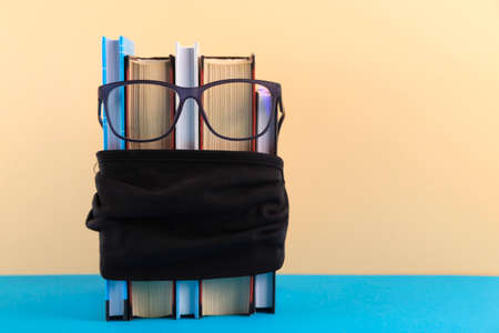 A stack of books with glasses and a protective black mask against the virus, social distance and medical recommendations for dealing with a pandemic in school. Фото со стока