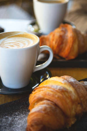 Cappuccino and croissants on a table in a coffee shop. Texture of baking and froth of a coffee drink