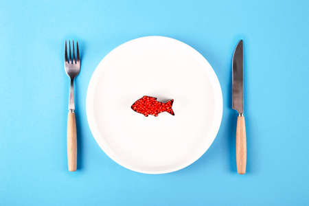 Plastic fish in a plate - harmful substances in food concept