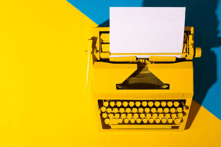Yellow bright typewriter on a yellow and blue background. Creativity concept