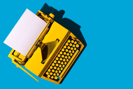 Yellow bright typewriter on blue background. Creativity concept