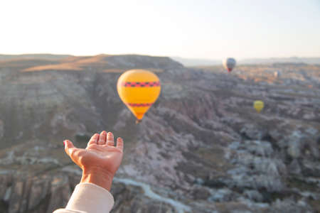 Flying balloons in the sky and female hands reaching for them