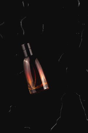 Mens perfume among the water on a black background. Stylish trending photo