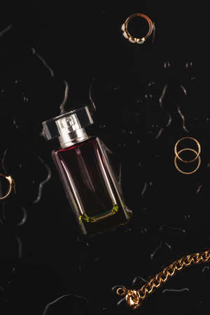 Beautiful accessories and womens perfume on a black background among the water