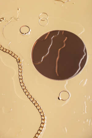 Gold womens jewelry next to a round mirror with water drops Banco de Imagens