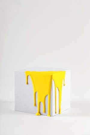 White cube with smudges of bright yellow paint color of the year 2021