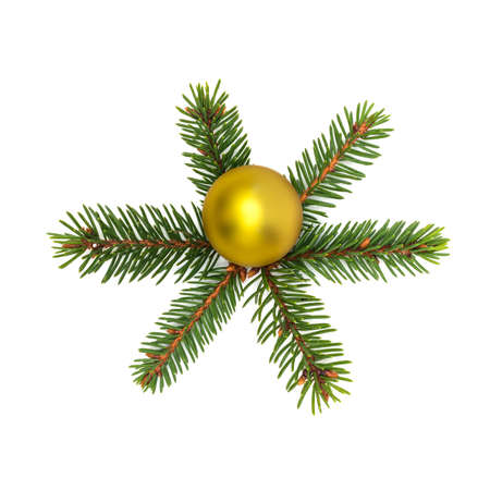 Small spruce branches laid out in form of a six-pointed snowflake with a yellow shiny ball in the center on a white background