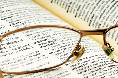 explanatory: Close-up word success through glasses in open book Stock Photo