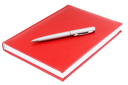 Red paper personal organizer and silver pen isolated on white photo