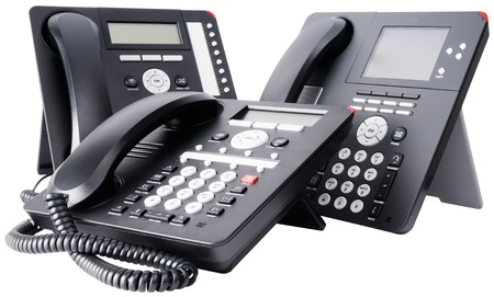 Three office digital multi-button telephone sets with LCD isolated on the white