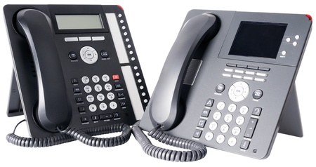 Two office digital multi-button telephone sets with LCD isolated on the white