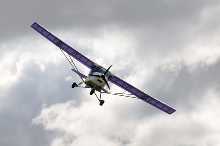 monoplane: Flying private propeller-driven airplane over cloud sky