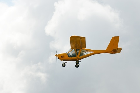 Flying private propeller-driven airplane over cloud sky