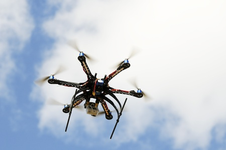 Hexacopter aircraft model in flight over blue sky