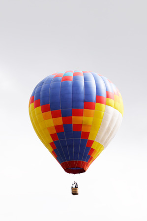 grey  sky: Colored balloon flying in summer grey sky Stock Photo