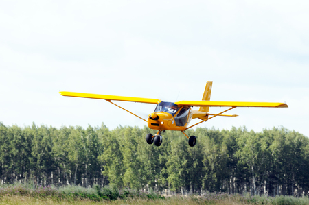 airplane landing: Private propeller-driven airplane landing over green trees Stock Photo