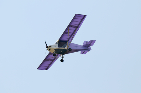 Flying private propeller-driven airplane over blue sky