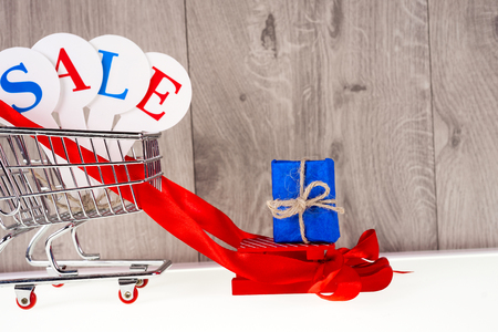 Shopping trolley with gift boxes on a wooden background. Holidays sale