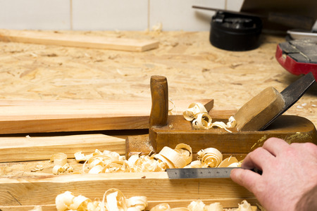 Carpenter working. tools on wooden table with sawdust.