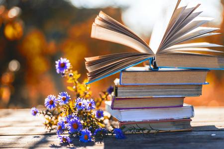 Otwórz książkę na drewnianym stole na naturalnym tle. Nieostrość