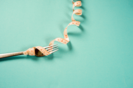fork and knife with a centimeter on a blue background, diet, healthy lifestyle.