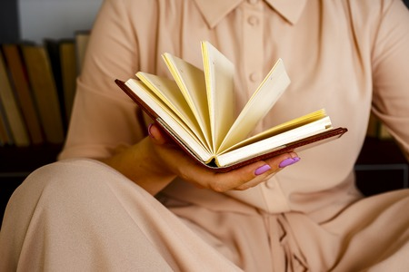 Young girl in a light dress is reading a book. Female hands hold a book in their hands