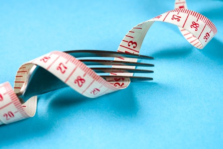 fork with centimeter on a blue background, diet, healthy lifestyle.
