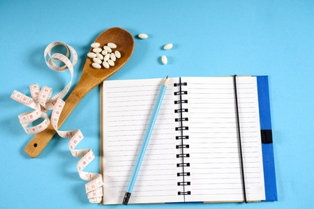 Sheet of Diet Plan and wooden spoon with a measuring tape on a blue background, diet, healthy lifestyle. Reklamní fotografie