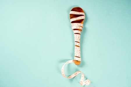Wooden spoon with a measuring tape on a blue background, diet, healthy lifestyle.
