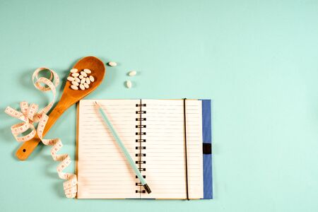 Sheet of Diet Plan and wooden spoon with a measuring tape on a blue background, diet, healthy lifestyle. 写真素材 - 130718045