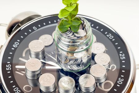 coins with plant and clock, isolated on white background. savings concept 写真素材 - 130718230