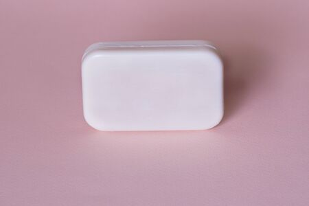Soap bar in foam with copy space in center isolated on bright pink background