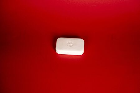 Soap bar in foam with copy space in center isolated on bright red background. Reklamní fotografie