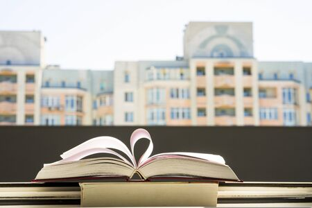 stack of books, pen oin the window with city view with top one opened and pages forming heart shape.