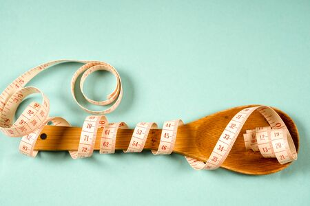 Wooden spoon with a measuring tape on a blue background, diet, healthy lifestyle 写真素材