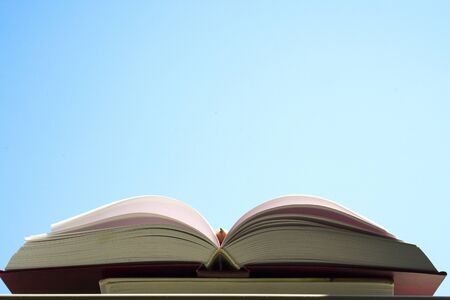 Open book, hardback books on bright colorful background. Blue sky. Back to school. Copy space for text. 写真素材