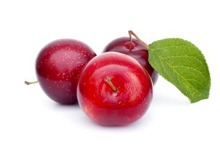 ciruela: Tres ciruelas maduras frescas con hoja