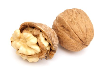 Two fresh walnuts on the white background. One of them is crashed