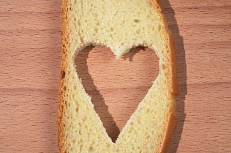 porosity: Piece of a white loaf with the cut out pulp in the form of heart on a wooden chopping board Stock Photo