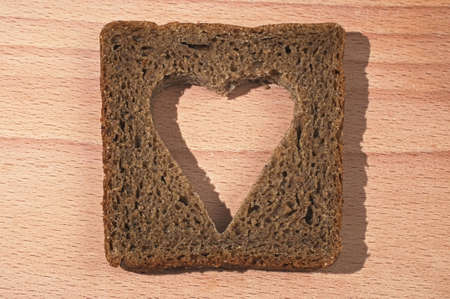 porosity: Piece of black bread with the cut out pulp in the form of heart on a wooden chopping board