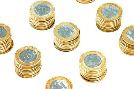 pillage: Brazilian real coins pile over white background.
