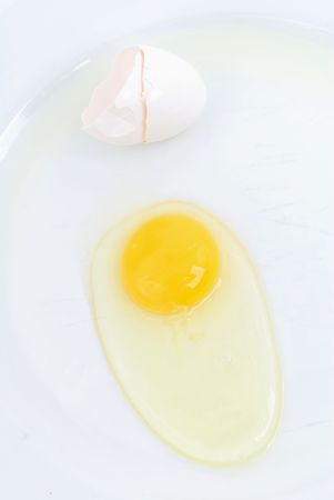 craked: Raw Egg outside the cracked sheel on the plate . Stock Photo