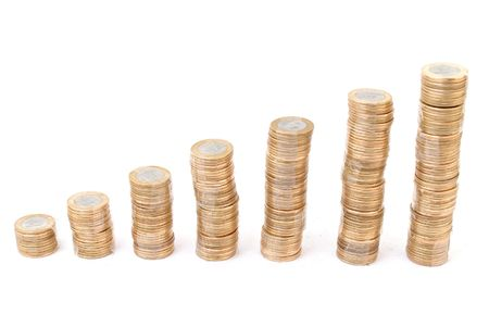 Pile of coins growing on white background . Stock Photo